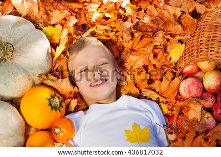 Smiling boy laying on the leaves with pumpkins