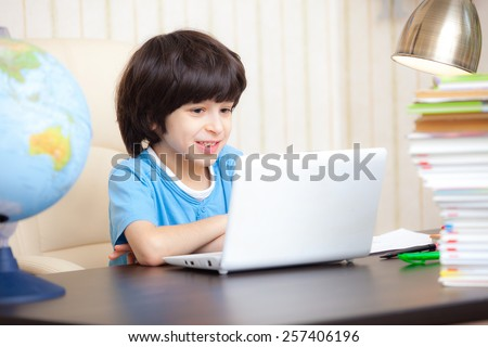 smiling boy looking at a computer monitor, distance learning - stock photo