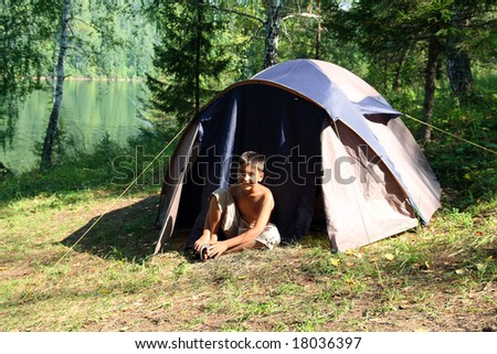 smiling boy near camping tent in forest - stock photo