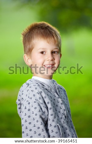Smiling boy of preschool age against a summer garden - stock photo