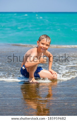 Smiling boy on beach with thumbs up and turquoise woter on background - stock photo