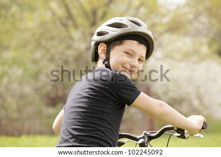 Smiling boy on bike looking over shoulder - stock photo