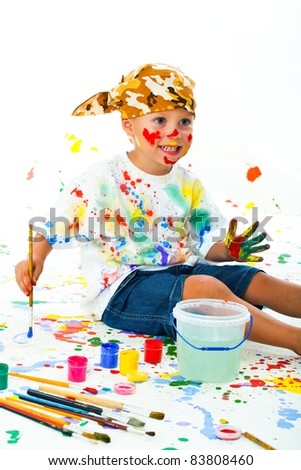 Smiling boy paints paints