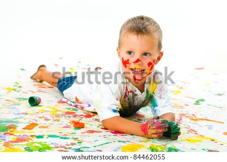 Smiling boy paints paints - stock photo