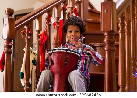 Smiling boy playing on drum. Young cheerful mulatto with drum. Let's here some traditional music. Talented djembe performer. - stock photo