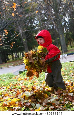 smiling boy plays with yellow leaves in an autumn time