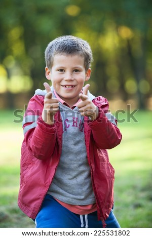 Smiling boy pointing with fingers to the camera, outdoors - stock photo