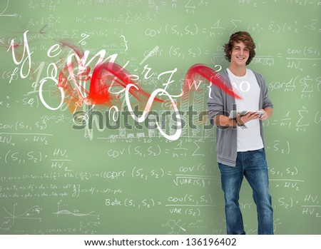 Smiling boy posing in front of chalk board in a classroom - stock photo