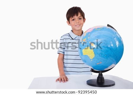 Smiling boy posing with a globe against a white background - stock photo