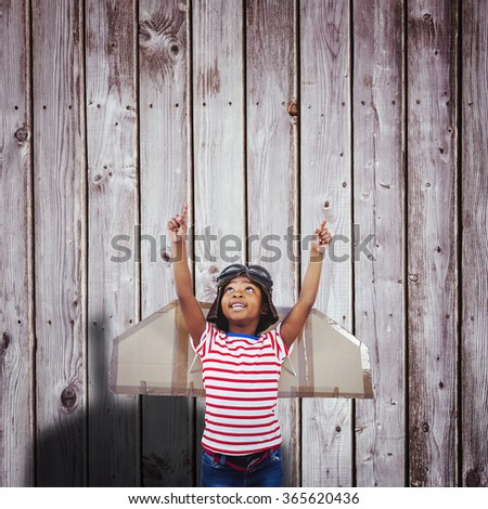 Smiling boy pretending to be pilot against digitally generated grey wooden planks - stock photo