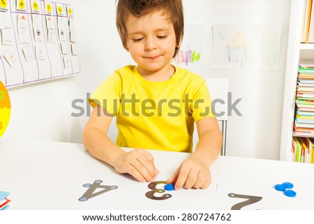 Smiling boy put coins on numbers learning count - stock photo