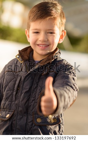 Smiling Boy Showing Thumb Up Sign, Outdoors - stock photo
