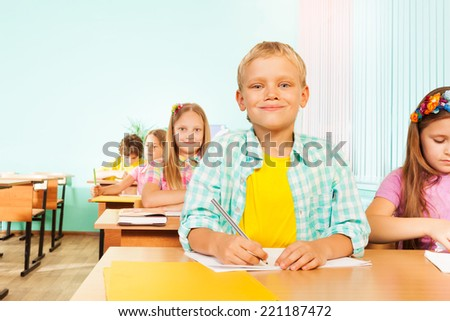 Smiling boy sits in class and holds pen to write