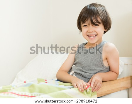 Smiling boy sitting in bed. Little boy going to bed. Happy Child at bedtime. Boy in gray tank top pajamas ready to sleep. A toddler bed with young brown haired boy sitting in it. Bedtime at home - stock photo