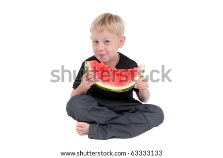 Smiling boy sitting on the floor with his legs crossed eating a slice of watermelon - stock photo