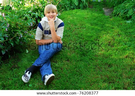 Smiling boy sitting on the grass in the park - stock photo