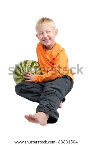 Smiling boy sitting with a watermelon on his side - stock photo