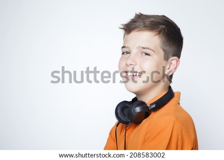 Smiling boy standing with headphones on the neck against grey background - stock photo
