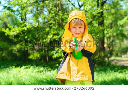 smiling boy stands on lawn in  summer park - stock photo