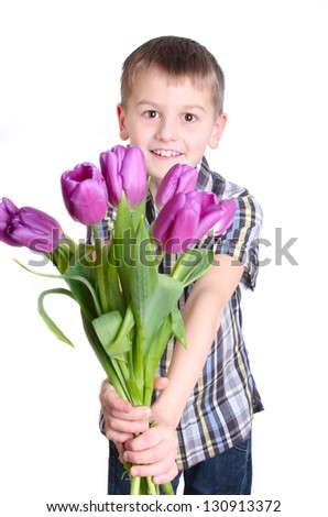 Smiling boy stretches forward bouquet of pink tulips isolated on white background