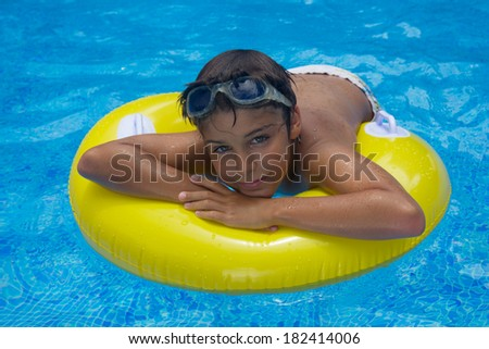 smiling boy taking sunbath in pool on rubber ring - stock photo