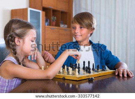 Smiling boy teaching little sister chess game at home - stock photo