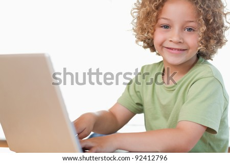 Smiling boy using a notebook in a kitchen - stock photo