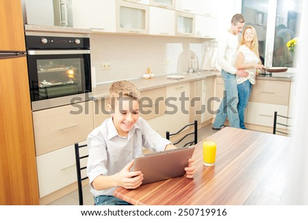 Smiling boy using digital tablet in the kitchen while his parents cooking dinner at the background. - stock photo