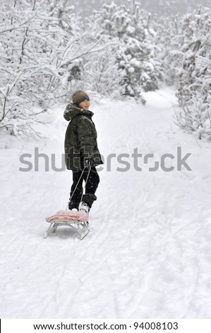 smiling boy walking with sleds in snow-covered winter forest - stock photo
