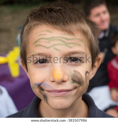 Smiling boy with face painted outdoors portrait. - stock photo