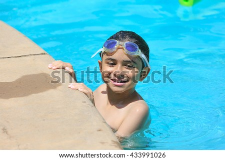 Smiling boy with goggles  in the pool border