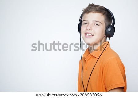 Smiling boy with headphones listening music against grey background - stock photo