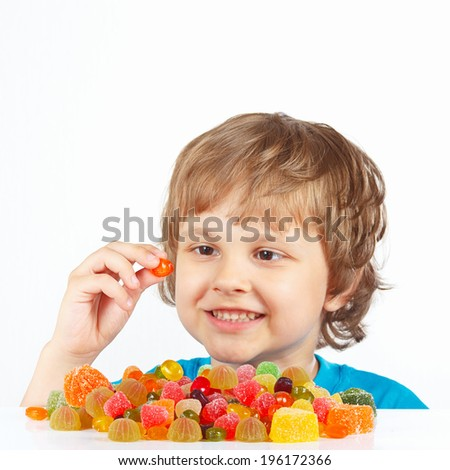 Smiling boy with jelly candies on a white background