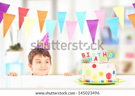 Smiling boy with party hat looking at a birthday cake at home - stock photo