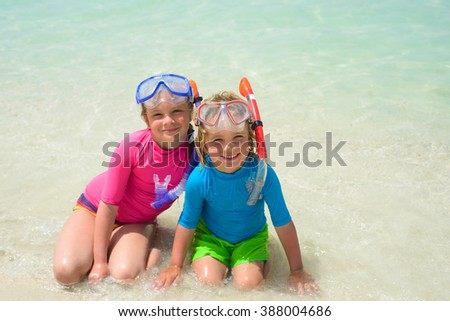 Smiling boy with sister wearing snorkeling gear  on the beach - stock photo