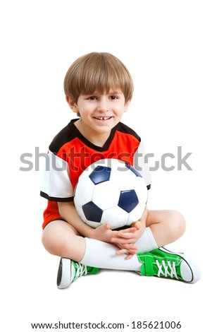 smiling boy with soccer ball sits on the floor