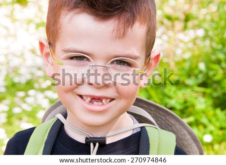 Smiling boy without front teeth, outdoors - stock photo