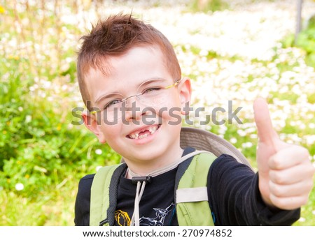 Smiling boy without front teeth showing his thumb up - stock photo