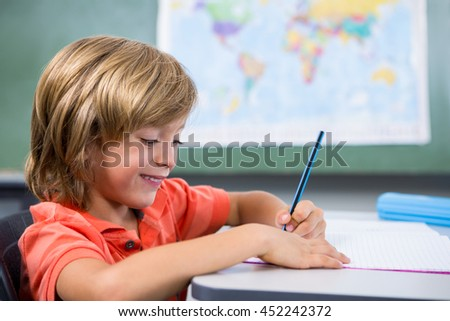 Smiling boy writing on book in classroom at school - stock photo