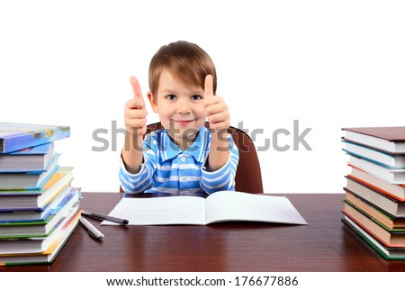 smiling boy 5 years at the desk shows a hands with a thumbs up. isolated on white background. horizontal - stock photo