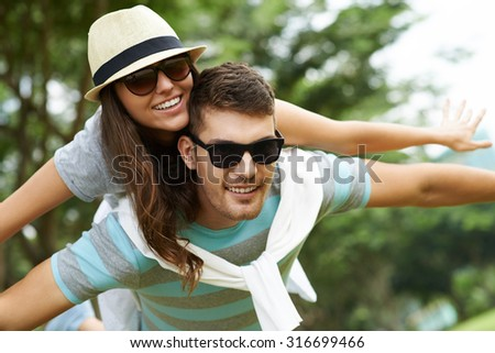 Smiling boyfriend giving piggyback ride to his girlfriend - stock photo