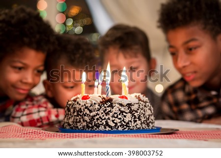 Smiling boys near birthday cake. Boys' birthday cake beside window. Wait till candles burn out. So interested and excited. - stock photo