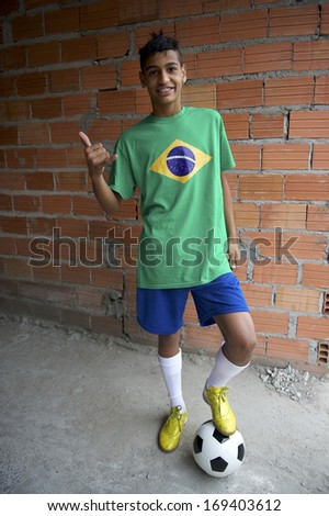 Smiling Brazilian teen wearing Brazilian flag t-shirt standing by rustic favela wall giving thumbs up with football soccer ball - stock photo