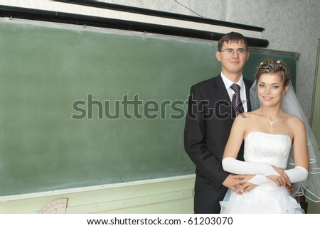 Smiling bride and groom standing next to blank blackboard in classroom