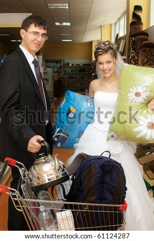 Smiling bride and groom with push cart with goods in store