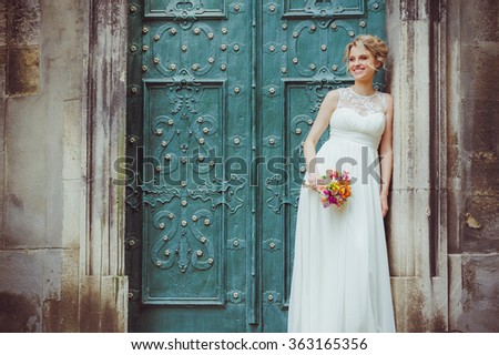 Smiling bride holding big wedding bouquet - stock photo