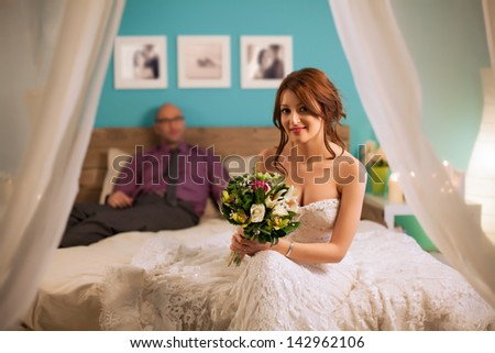 Smiling bride sitting on the bed in front of her husband. - stock photo