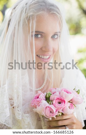 Smiling bride wearing veil over face holding bouquet looking at camera in the countryside