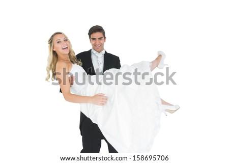 Smiling bridegroom lifting his wife up smiling at camera - stock photo