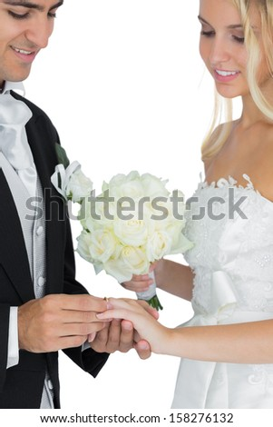 Smiling bridegroom putting the wedding ring on his wife's finger on white background - stock photo